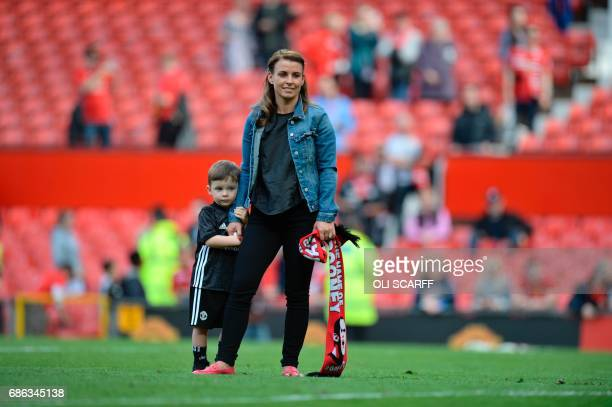 Manchester United's English striker Wayne Rooney's wife Coleen stands with their son Klay on the pitch at the end of the English Premier League...