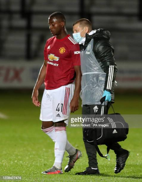 Manchester United's Ethan Laird leaves the field after picking up an injury during the EFL Trophy Northern Group B match at the Peninsula Stadium...