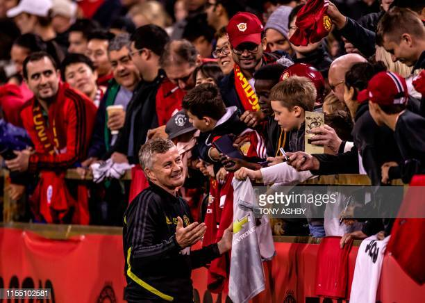 Manchester United's football manager Ole Gunnar Solkskjaer reacts with supporters after an open training session preparing for their preseason...