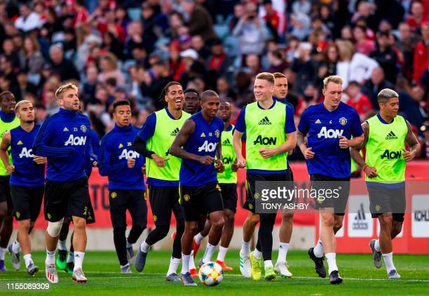 Manchester United's football players jog the boundary in front of supporters during an open training session preparing for their preseason friendly...
