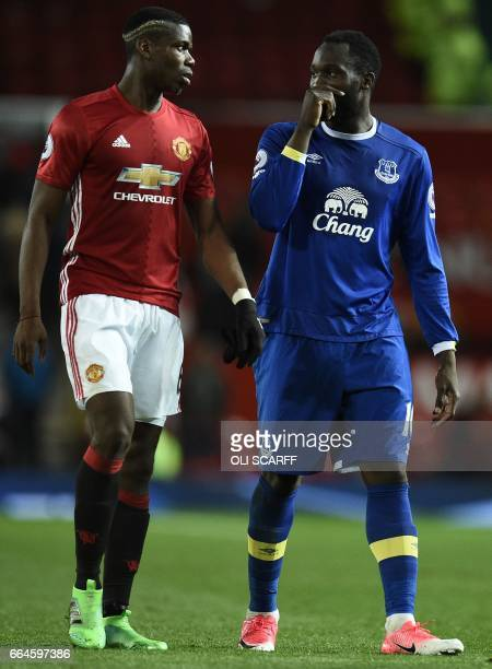 Manchester United's French midfielder Paul Pogba and Everton's Belgian striker Romelu Lukaku leave the pitch following the English Premier League...