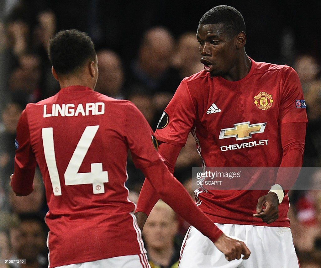 TOPSHOT - Manchester United's French midfielder Paul Pogba (R) and Manchester United's English midfielder Jesse Lingard (L) do a celebration dance after Pogba scored their third goal during the UEFA Europa League group A football match between Manchester United and Fenerbahce at Old Trafford in Manchester, north west England, on October 20, 2016. / AFP / OLI