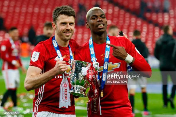 Manchester United's French midfielder Paul Pogba and Manchester United's English midfielder Michael Carrick celebrate with the trophy on the pitch...