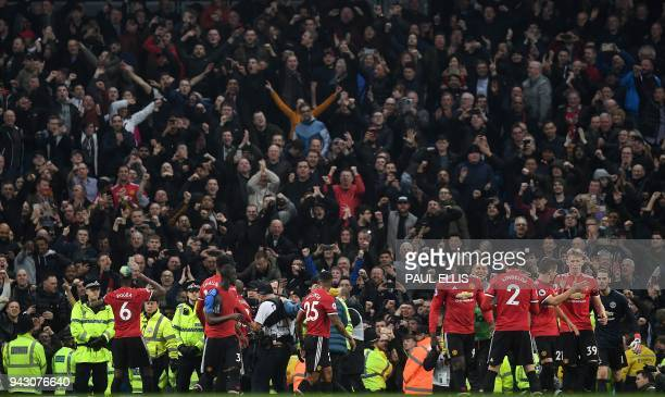 Manchester United's French midfielder Paul Pogba and teammates applaud the fans following during the English Premier League football match between...