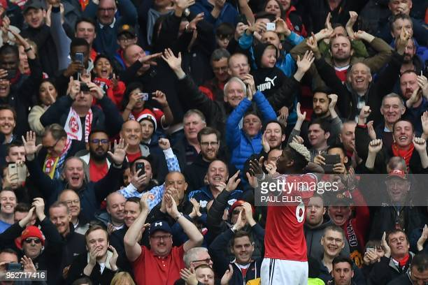 Manchester United's French midfielder Paul Pogba celebrates in front of the United fans after scoring the opening goal of the English Premier League...