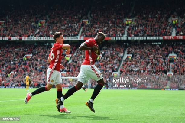Manchester United's French midfielder Paul Pogba celebrates scoring their second goal with Manchester United's English midfielder Josh Harrop during...