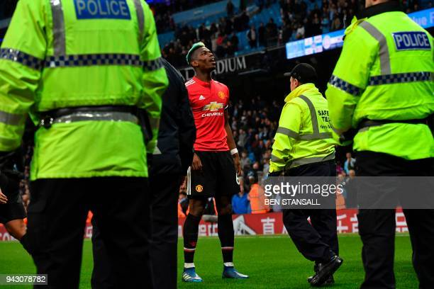 Manchester United's French midfielder Paul Pogba celebrates victory surrounded by security and police after the final whistle in the English Premier...