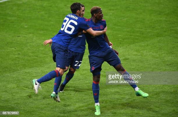 Manchester United's French midfielder Paul Pogba celebrates with his teammates Manchester United's Italian defender Matteo Darmian and Manchester...
