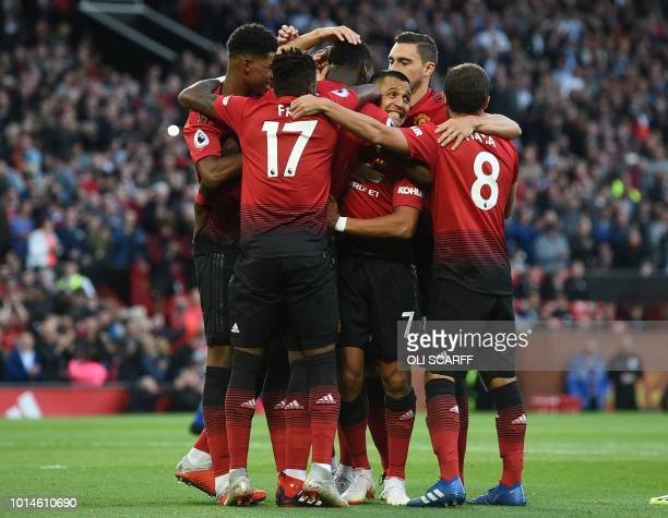 Manchester United's French midfielder Paul Pogba celebrates with teammates after scoring the opening penalty during the English Premier League...