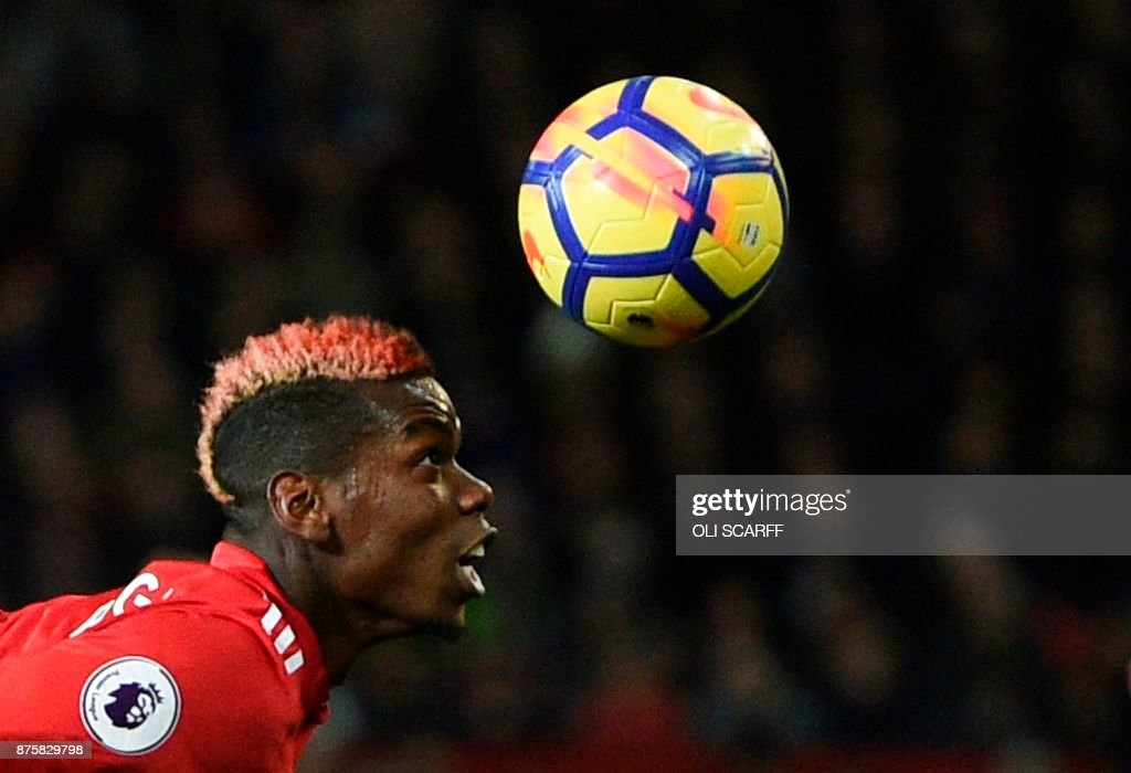 Manchester United's French midfielder Paul Pogba goes for a header during the English Premier League football match between Manchester United and Newcastle at Old Trafford in Manchester, north west England, on November 18, 2017. / AFP PHOTO / Oli SCARFF / RESTRICTED TO EDITORIAL USE. No use with unauthorized audio, video, data, fixture lists, club/league logos or 'live' services. Online in-match use limited to 75 images, no video emulation. No use in betting, games or single club/league/player publications. /