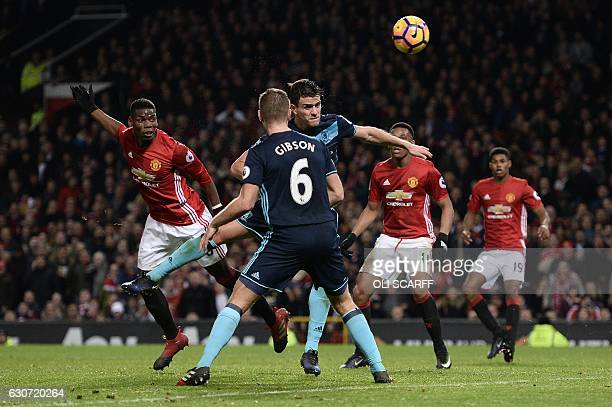Manchester United's French midfielder Paul Pogba heads the ball to score his team's second goal during the English Premier League football match...