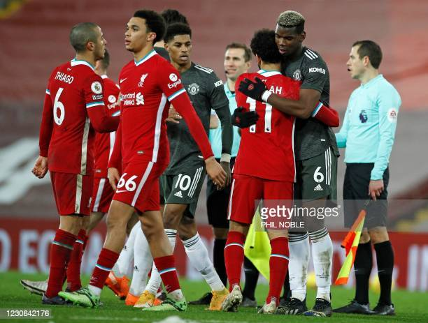 Manchester United's French midfielder Paul Pogba hugs Liverpool's Egyptian midfielder Mohamed Salah after the final whistle during the English...
