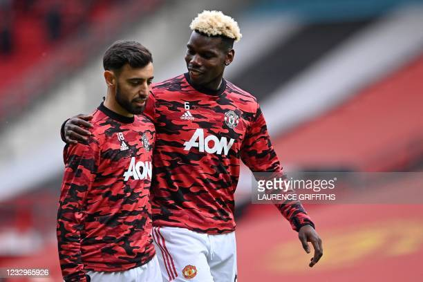 Manchester United's French midfielder Paul Pogba hugs Manchester United's Portuguese midfielder Bruno Fernandes as they warm up ahead of the English...