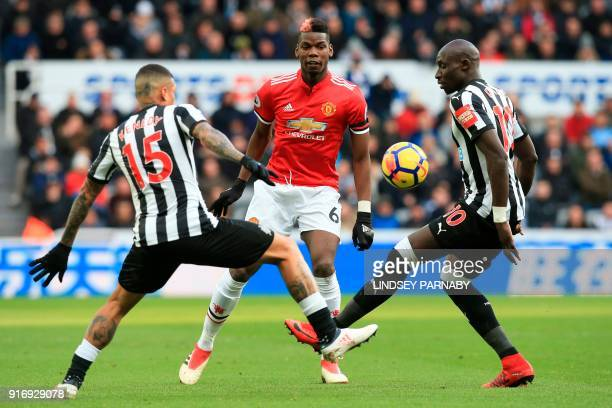 Manchester United's French midfielder Paul Pogba is challenged by Newcastle United's Senegalese midfielder Mohamed Diame and Newcastle United's...
