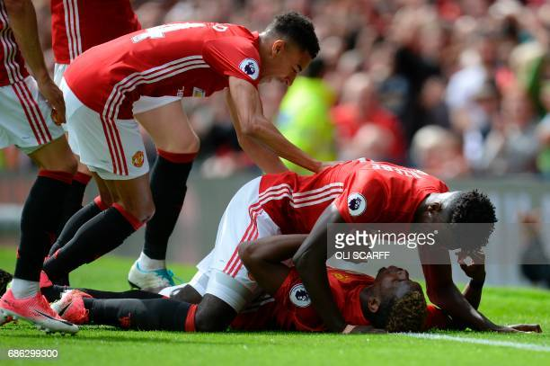Manchester United's French midfielder Paul Pogba is congratulated by teammates after scoring their second goal during the English Premier League...