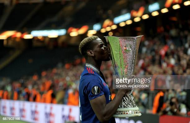 Manchester United's French midfielder Paul Pogba kisses the trophy after his team won the UEFA Europa League final football match Ajax Amsterdam v...
