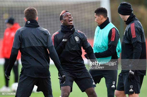 Manchester United's French midfielder Paul Pogba laughs during a team training session at the club's training complex near Carrington west of...