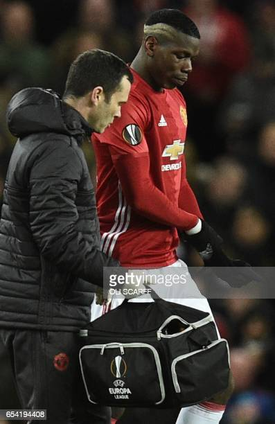 Manchester United's French midfielder Paul Pogba leaves the field injured during the UEFA Europa League round of 16 secondleg football match between...