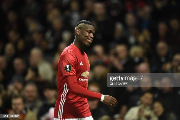 Manchester United's French midfielder Paul Pogba leaves the pitch injured during the UEFA Europa League round of 16 second-leg football match between...