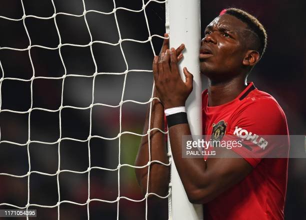 TOPSHOT Manchester United's French midfielder Paul Pogba reacts after missing a chance during the English League Cup third round football match...
