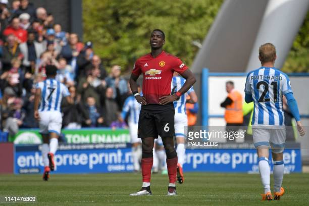 TOPSHOT Manchester United's French midfielder Paul Pogba reacts after Huddersfield score their first goal during the English Premier League football...