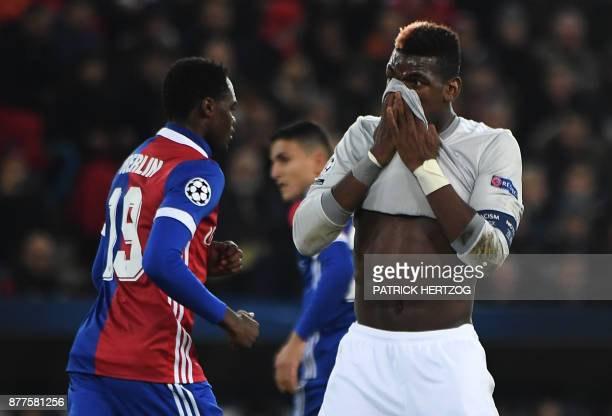 Manchester United's French midfielder Paul Pogba reacts as Basel's Swiss forward Dimitri Oberlin walks past during the UEFA Champions League Group A...