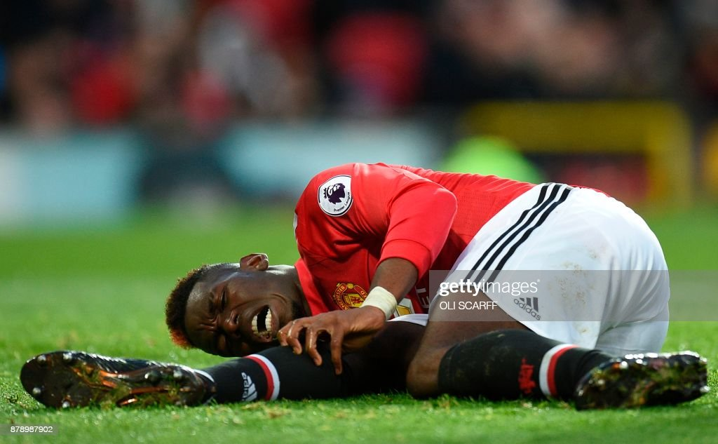 Manchester United's French midfielder Paul Pogba reacts on the pitch with an injury during the English Premier League football match between Manchester United and Brighton and Hove Albion at Old Trafford in Manchester, north west England, on November 25, 2017. / AFP PHOTO / Oli SCARFF / RESTRICTED TO EDITORIAL USE. No use with unauthorized audio, video, data, fixture lists, club/league logos or 'live' services. Online in-match use limited to 75 images, no video emulation. No use in betting, games or single club/league/player publications. /