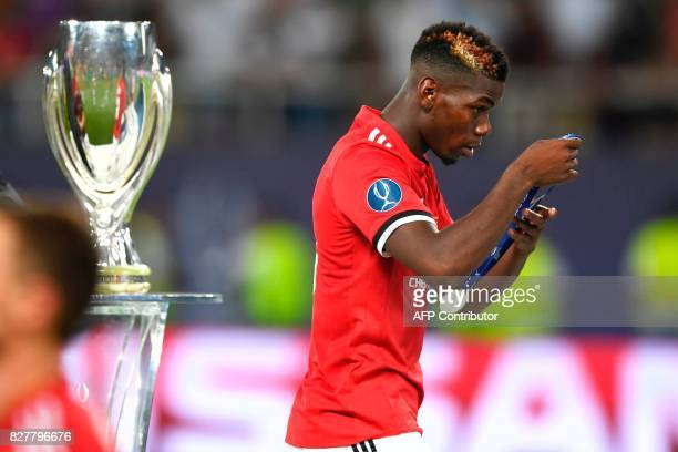 Manchester United's French midfielder Paul Pogba removes his medal after losing the UEFA Super Cup football match between Real Madrid and Manchester...