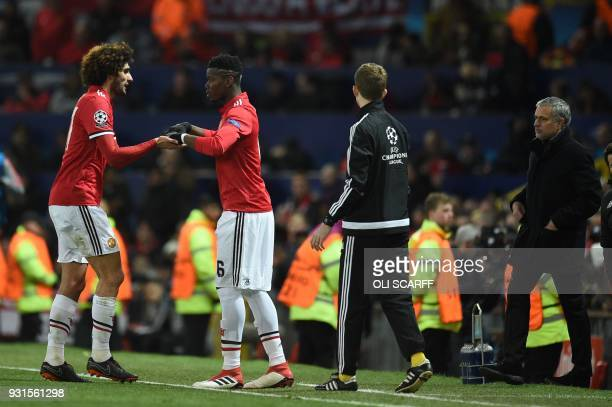 Manchester United's French midfielder Paul Pogba replaces Manchester United's Belgian midfielder Marouane Fellaini during a last 16 second leg UEFA...