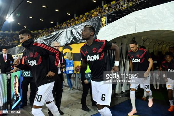 Manchester United's French midfielder Paul Pogba runs onto the pitch to warm up with teammates Manchester United's English striker Marcus Rashford...