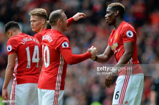 Manchester United's French midfielder Paul Pogba shakes hands with Manchester United's English striker Wayne Rooney after scoring their second goal...