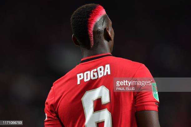 Manchester United's French midfielder Paul Pogba shows off his new hairstyle during the English League Cup third round football match between...