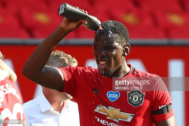 Manchester United's French midfielder Paul Pogba sprays himself with water to cool down during a drinks break in the English Premier League football...