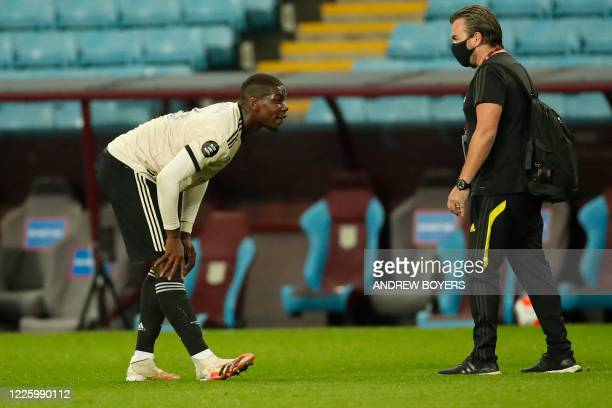 Manchester United's French midfielder Paul Pogba stretches his leg after going down near the end of the English Premier League football match between...