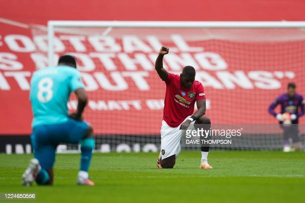 Manchester United's French midfielder Paul Pogba takes a knee to show support for the Black Lives Matter movement and protest against racism during...