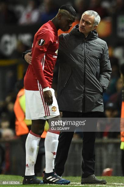 Manchester United's French midfielder Paul Pogba talks with Manchester United's Portuguese manager Jose Mourinho as he leaves the pitch injured and...