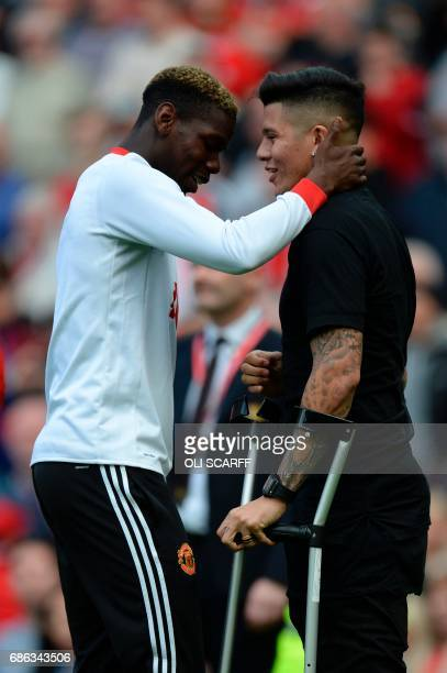 Manchester United's French midfielder Paul Pogba talks with the injured Manchester United's Argentinian defender Marcos Rojo during the English...