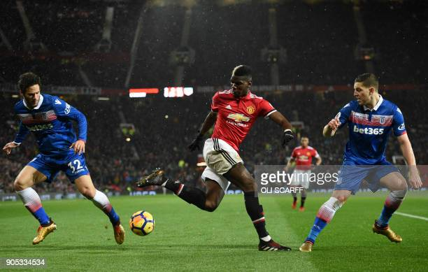 TOPSHOT Manchester United's French midfielder Paul Pogba tangles with Stoke City's Egyptian midfielder Ramadan Sobhi and Stoke City's Austrian...