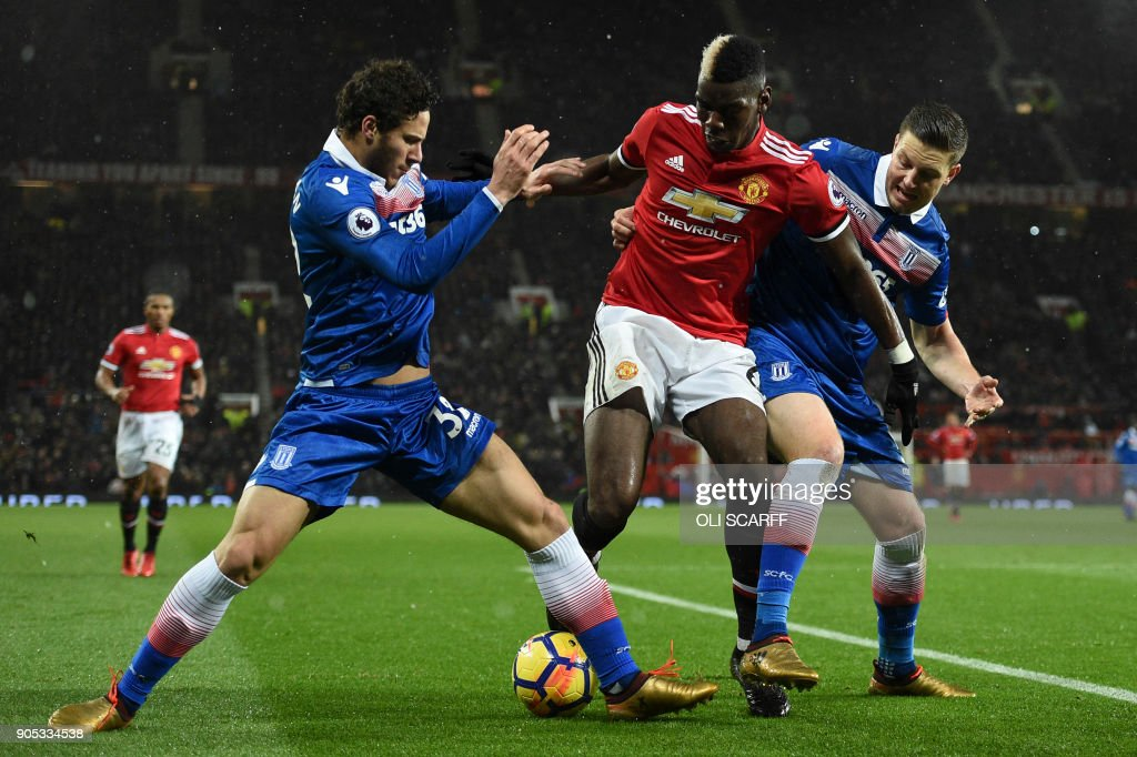 TOPSHOT - Manchester United's French midfielder Paul Pogba (C) tangles with Stoke City's Egyptian midfielder Ramadan Sobhi (L) and Stoke City's Austrian defender Kevin Wimmer (R) during the English Premier League football match between Manchester United and Stoke City at Old Trafford in Manchester, north west England, on January 15, 2018. / AFP PHOTO / Oli SCARFF / RESTRICTED TO EDITORIAL USE. No use with unauthorized audio, video, data, fixture lists, club/league logos or 'live' services. Online in-match use limited to 75 images, no video emulation. No use in betting, games or single club/league/player publications. /