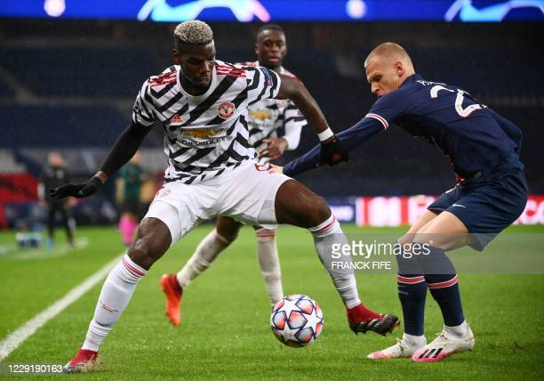 Manchester United's French midfielder Paul Pogba vies for the ball with Paris Saint-Germain's Dutch defender Mitchel Bakker during the UEFA Champions...