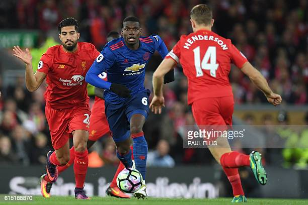 Manchester United's French midfielder Paul Pogba vies with Liverpool's English midfielder Jordan Henderson and Liverpool's German midfielder Emre Can...