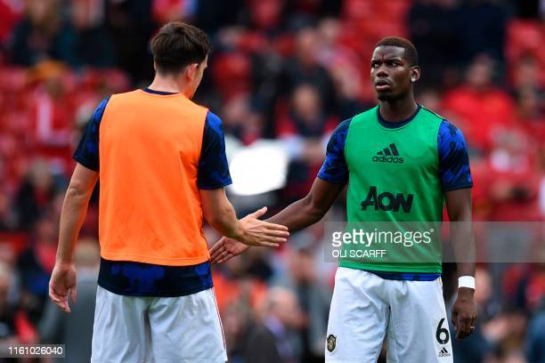 Manchester United's French midfielder Paul Pogba warms up with Manchester United's English defender Harry Maguire during the English Premier League...
