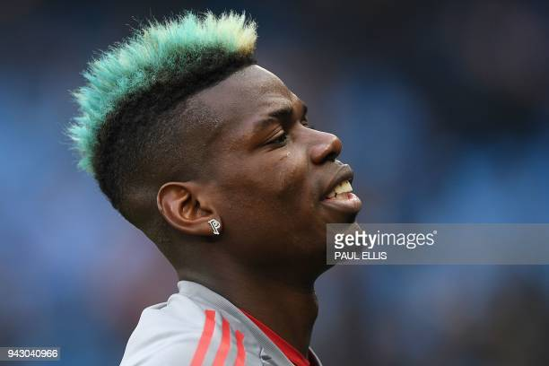 Manchester United's French midfielder Paul Pogba with his hair dyed blue warms up ahead of the English Premier League football match between...