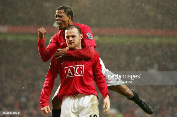 Manchester United's French player Patrice Evra and goal scorer Wayne Rooney celebrate after Rooney scored the third goal of the match during their...