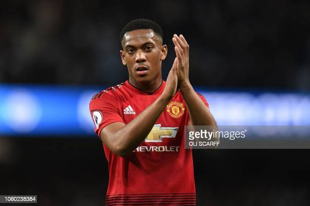 Manchester United's French striker Anthony Martial applauds fans after losing the English Premier League football match between Manchester City and...