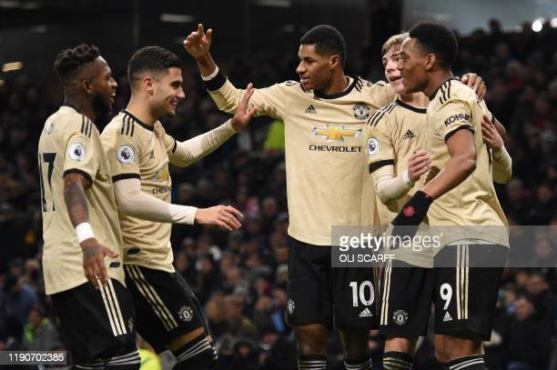 Manchester United's French striker Anthony Martial celebrates scoring the opening goal with team-mates Manchester United's Brazilian midfielder Fred,...