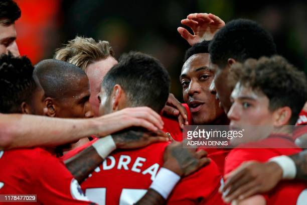 Manchester United's French striker Anthony Martial celebrates with teammates after scoring their third goal during the English Premier League...