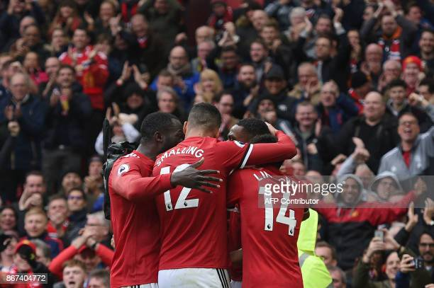 Manchester United's French striker Anthony Martial celebrates with teammates after scoring the opening goal of the English Premier League football...