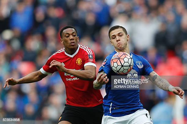 Manchester United's French striker Anthony Martial challenges Everton's Bosnian midfielder Muhamed Besic during the English FA Cup semifinal football...
