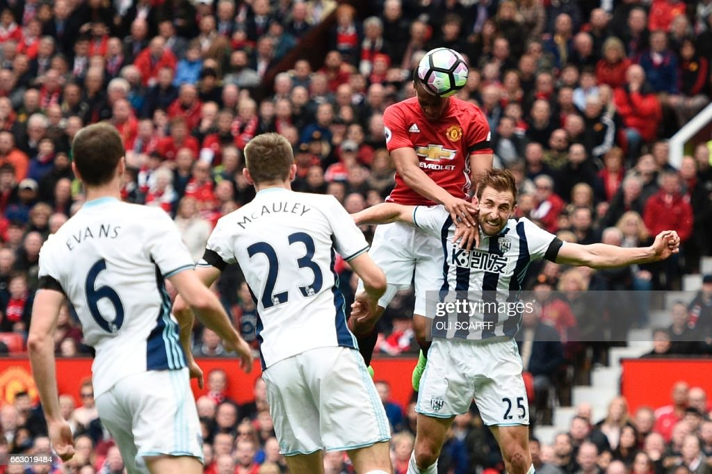 Manchester United's French striker Anthony Martial (2R) climbs above West Bromwich Albion's English defender Craig Dawson (R) but heads wide during the English Premier League football match between Manchester United and West Bromwich Albion at Old Trafford in Manchester, north west England, on April 1, 2017. / AFP PHOTO / Oli SCARFF / RESTRICTED TO EDITORIAL USE. No use with unauthorized audio, video, data, fixture lists, club/league logos or 'live' services. Online in-match use limited to 75 images, no video emulation. No use in betting, games or single club/league/player publications. /